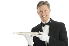 Confident Waiter In Tuxedo Holding Serving Tray. Portrait of confident waiter in tuxedo holding serving tray against white background Stock Images