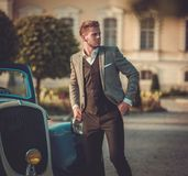 Confident wealthy man near classic convertible. Confident wealthy young man with newspaper near classic convertible Royalty Free Stock Images