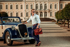 Confident wealthy young man with briefcase near classic convertible.  Stock Photo
