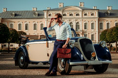 Confident wealthy young man with briefcase near classic convertible.  Stock Image