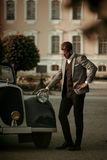 Confident wealthy young man near classic convertible.  Stock Photography