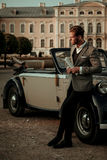 Confident wealthy young man with newspaper near classic convertible.  Royalty Free Stock Photography