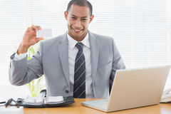 Confident well dressed man with business card at office desk Royalty Free Stock Images