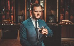 Confident well-dressed man with glass of whisky in Luxury apartment interior. royalty free stock images