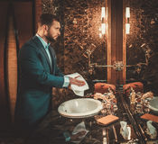 Confident well-dressed man in Luxury bathroom interior. Royalty Free Stock Photo