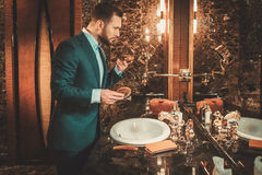 Confident well-dressed man in Luxury bathroom interior. Royalty Free Stock Image
