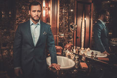 Confident well-dressed man in Luxury bathroom interior. Royalty Free Stock Photography