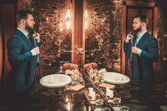 Confident well-dressed man in Luxury bathroom interior. Stock Photos