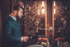 Confident well-dressed man in Luxury bathroom interior. Confident well-dressed man combing hair in luxury bathroom interior Royalty Free Stock Images