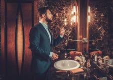 Confident well-dressed man in Luxury bathroom interior. Confident well-dressed man using perfume in luxury bathroom interior Stock Images