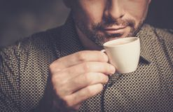 Confident well-groomed bearded man  with cup of coffee on dark background. Stock Photos