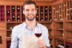 Confident winemaker. Confident young man in apron holding glass with red wine while standing in wine cellar Royalty Free Stock Images