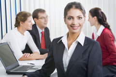 Confident woman. Portrait of a confident woman with her business team on the background Royalty Free Stock Photo