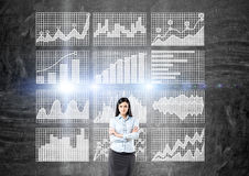 Confident woman against business charts Stock Image