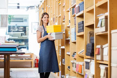 Confident Woman Carrying Boxes In Store. Portrait of confident mid adult woman carrying boxes in store Royalty Free Stock Images