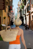Confident woman carrying a straw shopping bag. Walking away down a narrow urban street wearing a summer top and trendy straw hat while on vacation Stock Images