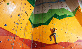 Confident woman climbing up the orange wall in gym Stock Images