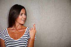 Confident woman crossing fingers while looking away Stock Images