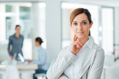 Confident woman entrepreneur posing in her office Royalty Free Stock Image