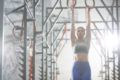Confident woman exercising with gymnastic rings in crossfit gym Royalty Free Stock Image