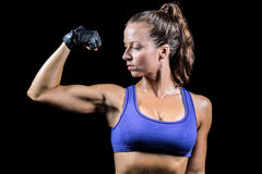 Confident woman flexing muscles. Against black background Royalty Free Stock Image