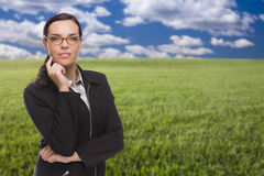 Confident Woman in Grass Field Looking At Camera Stock Photo
