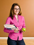 Confident woman holding apple and school books. Confident woman holding an apple and school books Royalty Free Stock Photography