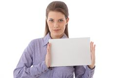 Confident woman holding blank sheet in studio Royalty Free Stock Images