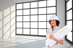 Confident woman holding construction plans. Composite image of confident woman holding construction plans Royalty Free Stock Image
