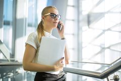 Confident Woman In Office Wear And Classic Glasses And Paper Documents In Hand Having Cell Telephone Conversation Royalty Free Stock Photos