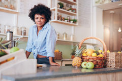 Confident woman juice bar owner. Portrait of confident young woman standing at counter in juice bar looking at camera. African female juice bar owner royalty free stock photo