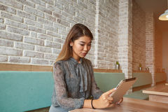 Confident woman lawyer is using digital table. Female financier is reading financial news in internet via touch pad during work break in modern cafe. Confident Stock Photos