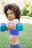 Confident woman lifting dumbbell Royalty Free Stock Photos