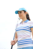 Confident woman looking away while holding golf club against clear sky. Confident women looking away while holding golf club against clear sky royalty free stock photos