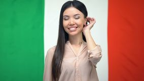 Confident woman looking at camera against Italian flag background, citizenship. Stock footage stock video footage