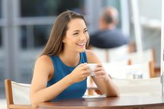 Confident woman looking at side in a coffee shop. Confident woman smiling looking at side sitting in a coffee shop terrace stock photos