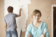 Confident Woman With Man Using Paint Roller Royalty Free Stock Images