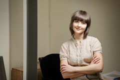Confident woman in office. Confident yiung smiling woman in office Royalty Free Stock Photography
