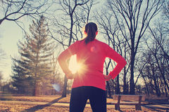 Confident woman preparing for a morning run outdoors in a park. A confident woman stands with her hands on her hips as she prepares for a morning jog in the park Royalty Free Stock Images