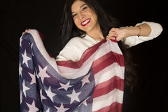 Confident woman proudly holding an American flag scarf Stock Images