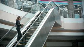 Confident woman is reading e-mail in internet via mobile phone, while is standing in shopping center on escalator stock video