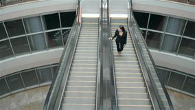 Confident woman is reading e-mail in internet via mobile phone, while is standing in shopping center on escalator stock video footage