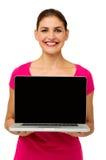 Confident Woman Showing Laptop. Portrait of confident mid adult woman showing laptop against white background. Vertical shot Stock Photography