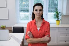 Confident woman standing with arms crossed. In kitchen Stock Image