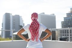Confident woman standing in city for breast cancer awareness. Against urban background stock photography