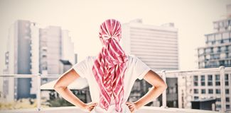 Confident woman standing in city for breast cancer awareness. Against urban background stock photo