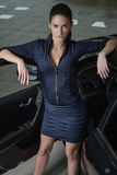 Confident woman standing and leaning her elbows to an open car door royalty free stock image