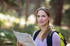 Confident woman standing with map Stock Image