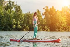 Confident woman standing with a paddle on the surfboard, SUP. Sport. Hobby. Yoga royalty free stock photo