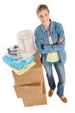 Confident Woman Standing By Stacked Boxes. Full length portrait of confident young woman standing by stacked cardboard boxes with towels; adhesive tape and lamp Stock Photos